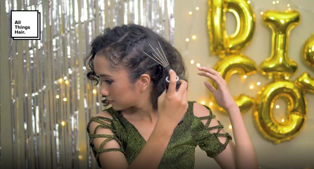 Wanita asia dengan rambut hitam keriting menyemprotkan hairspray pada rambut tebal dan keriting