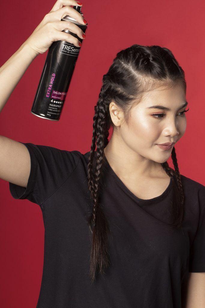 Wanita asia rambut hitam menyemprotkan hairspray pada rambut