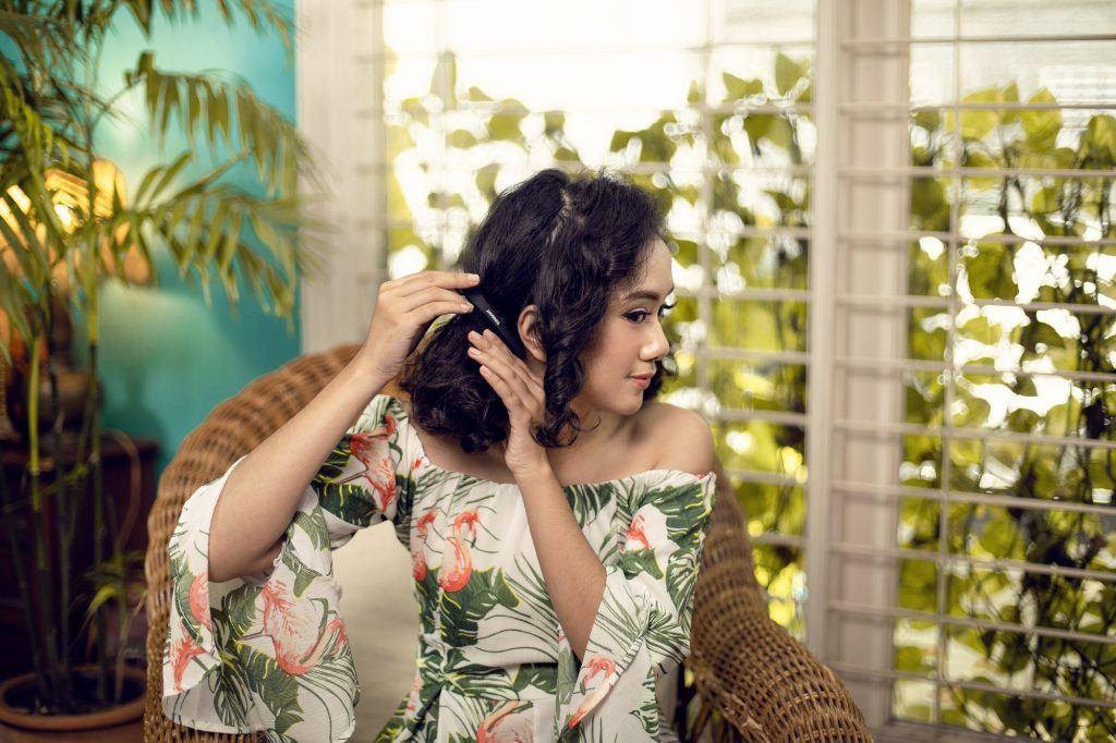 Wanita berambut keriting sedang menjepit rambut bagian belakang.