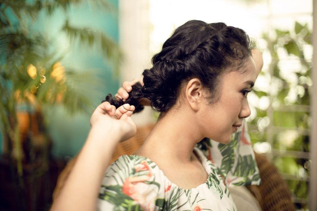 Wanita berambut keriting sedang memberikan cara menata rambut untuk festival musik