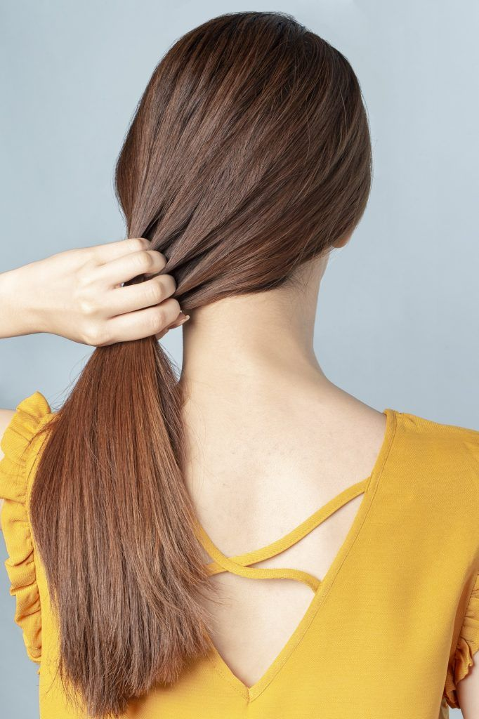 Wanita menarik ikat rambut, menarik rambutnya ke dalam menggunakan jepit rambut.