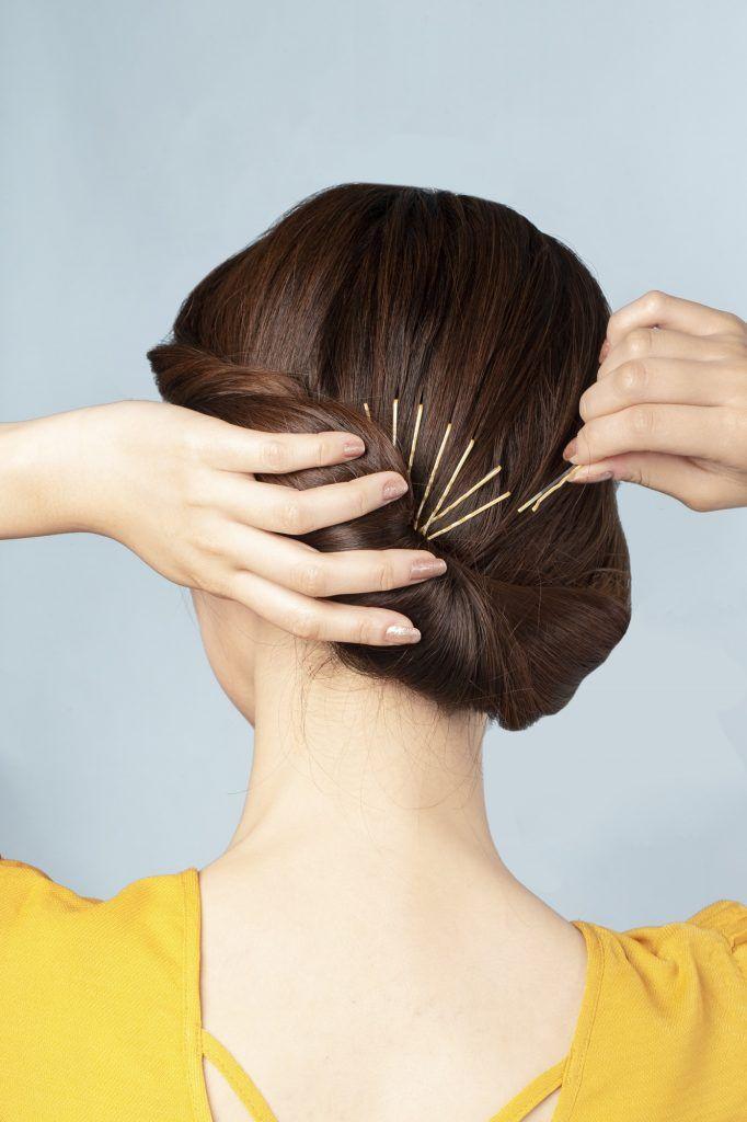 Wanita sedang menggunakan jepit rambut di rambut bagian belakang.