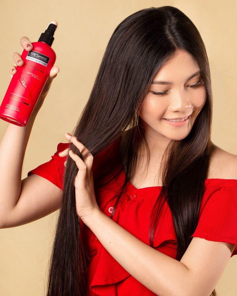 wanita asia dengan menyemprot heat protection spray sebelum mengeriting rambut