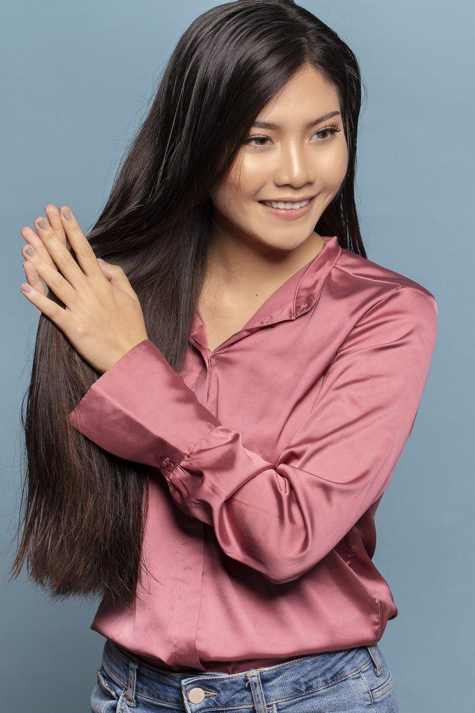 wanita asia menggunakan vitamin sebelum meluruskan rambut dengan scrunchie