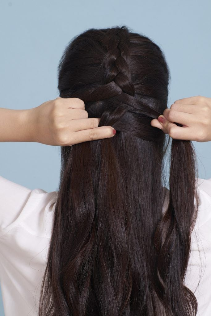 wanita asia sedang mengepang rambut panjang untuk membuat sanggul kepang gaya messy