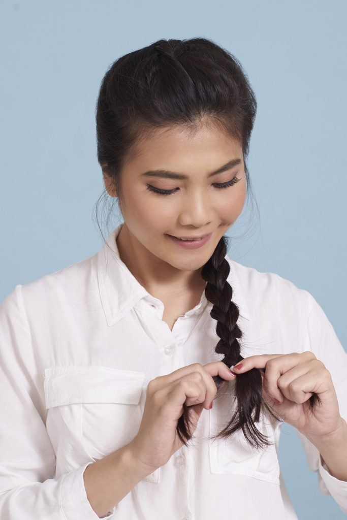 wanita asia sedang mengikat rambut panjang untuk membuat sanggul kepang gaya messy