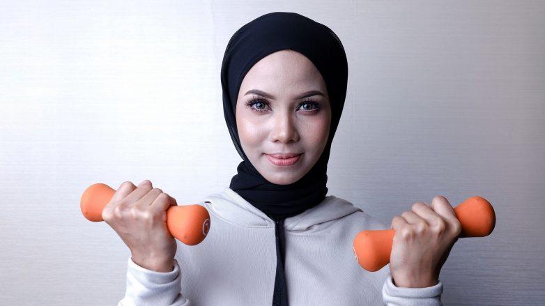 Wanita berhijab memegang barbel di kedua tangannya.