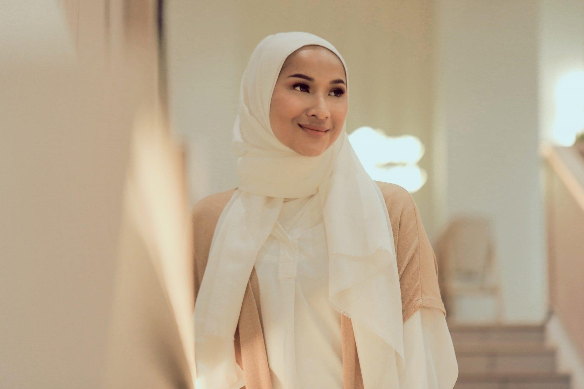 Wanita Asia memakai hijab pashmina bergaya semiformal berwarna putih