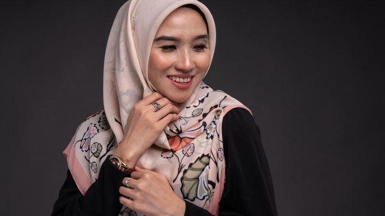 Wanita Asia memakai jilbab voile motif dengan gaya menutup dada.