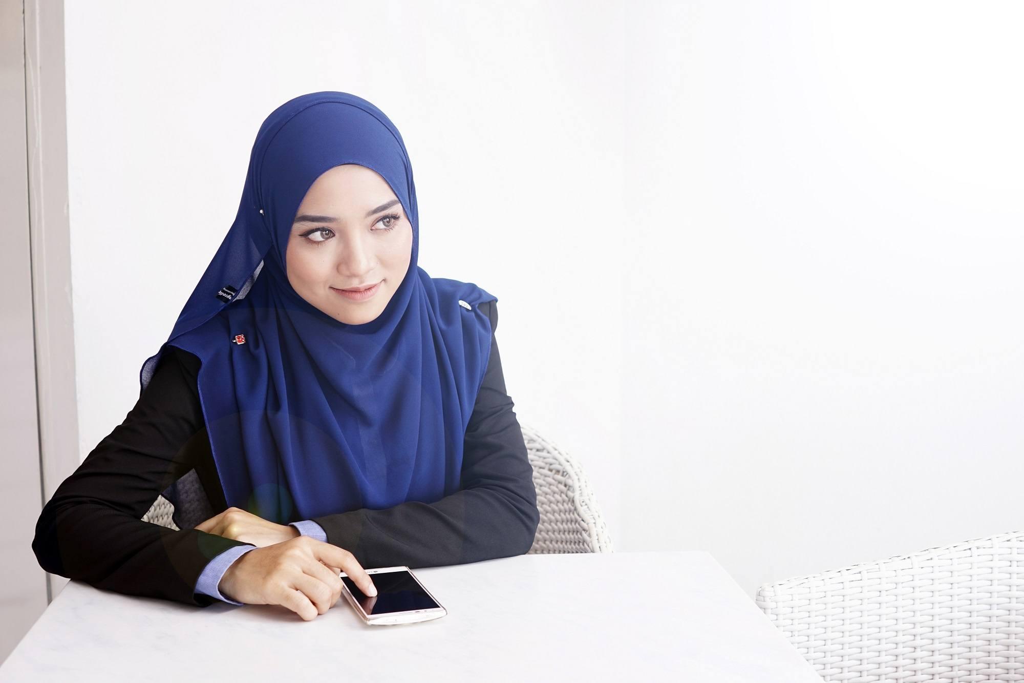 Wanita berhijab pashmina sedang duduk di meja kantor