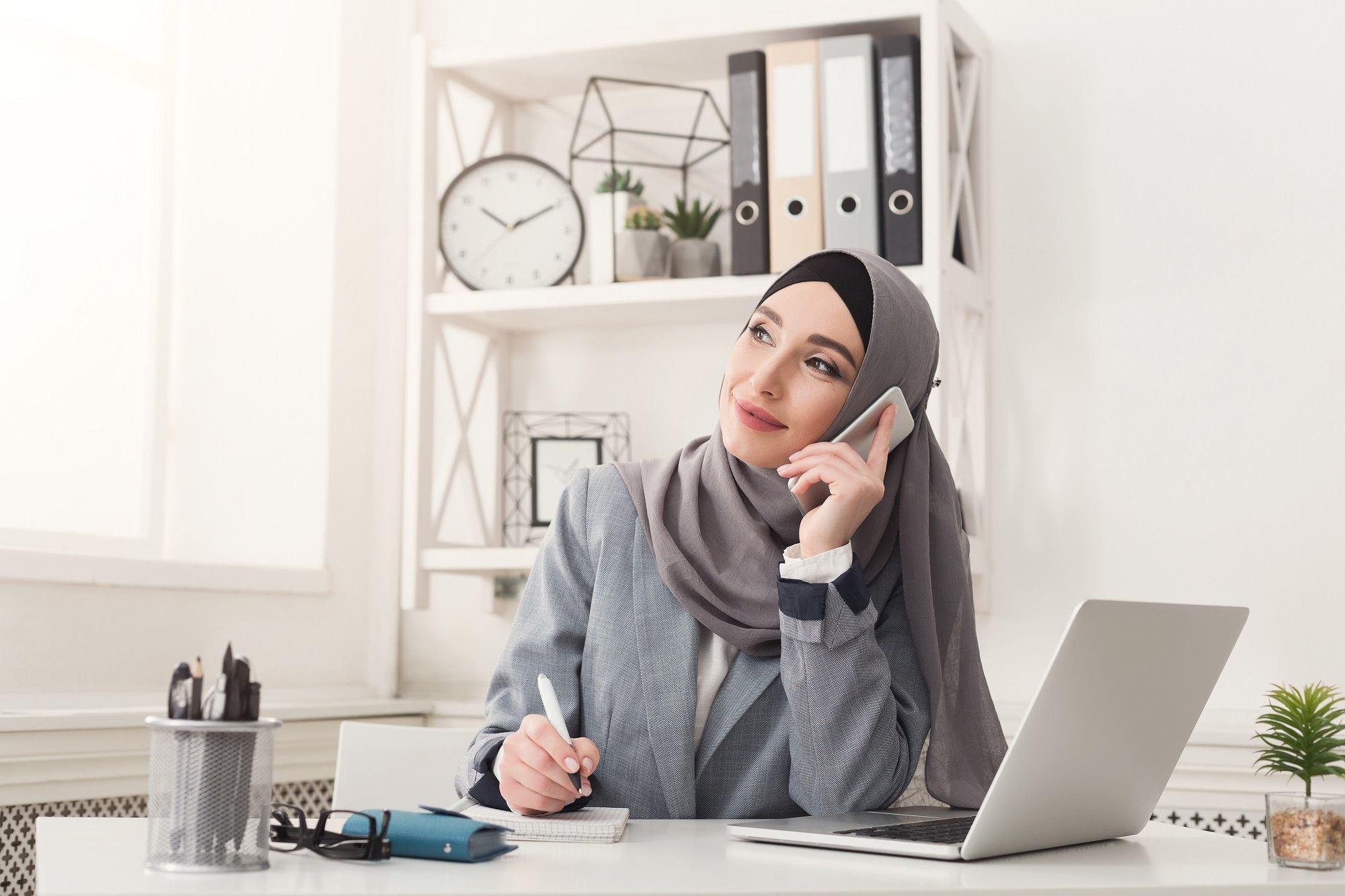 Seorang wanita berhijab sedang menelepon klien di kantor