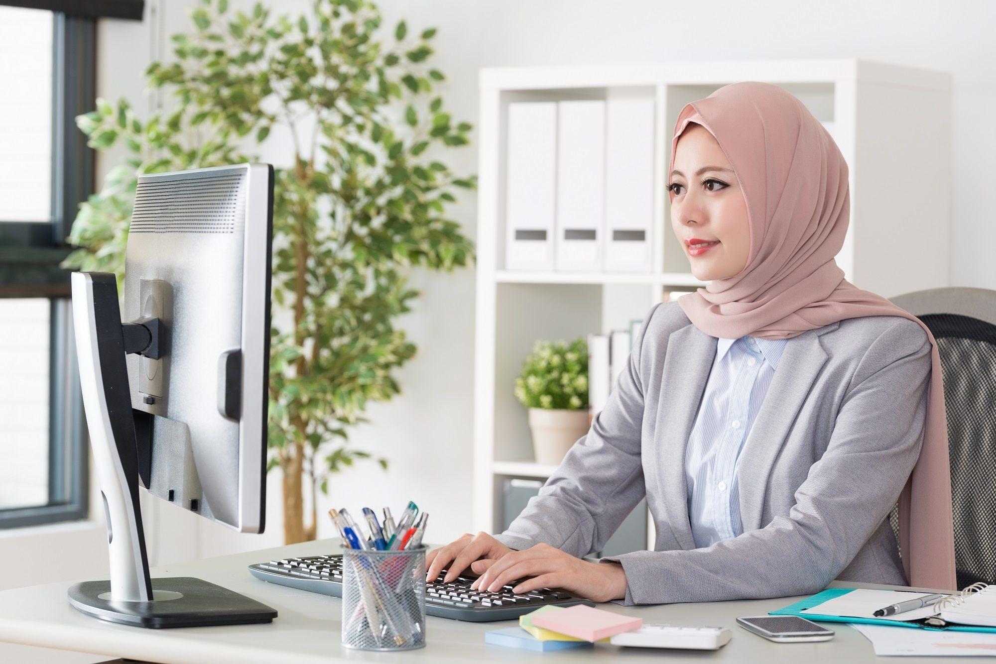 Seorang wanita memakai model hijab simple sedang duduk di meja kantor.
