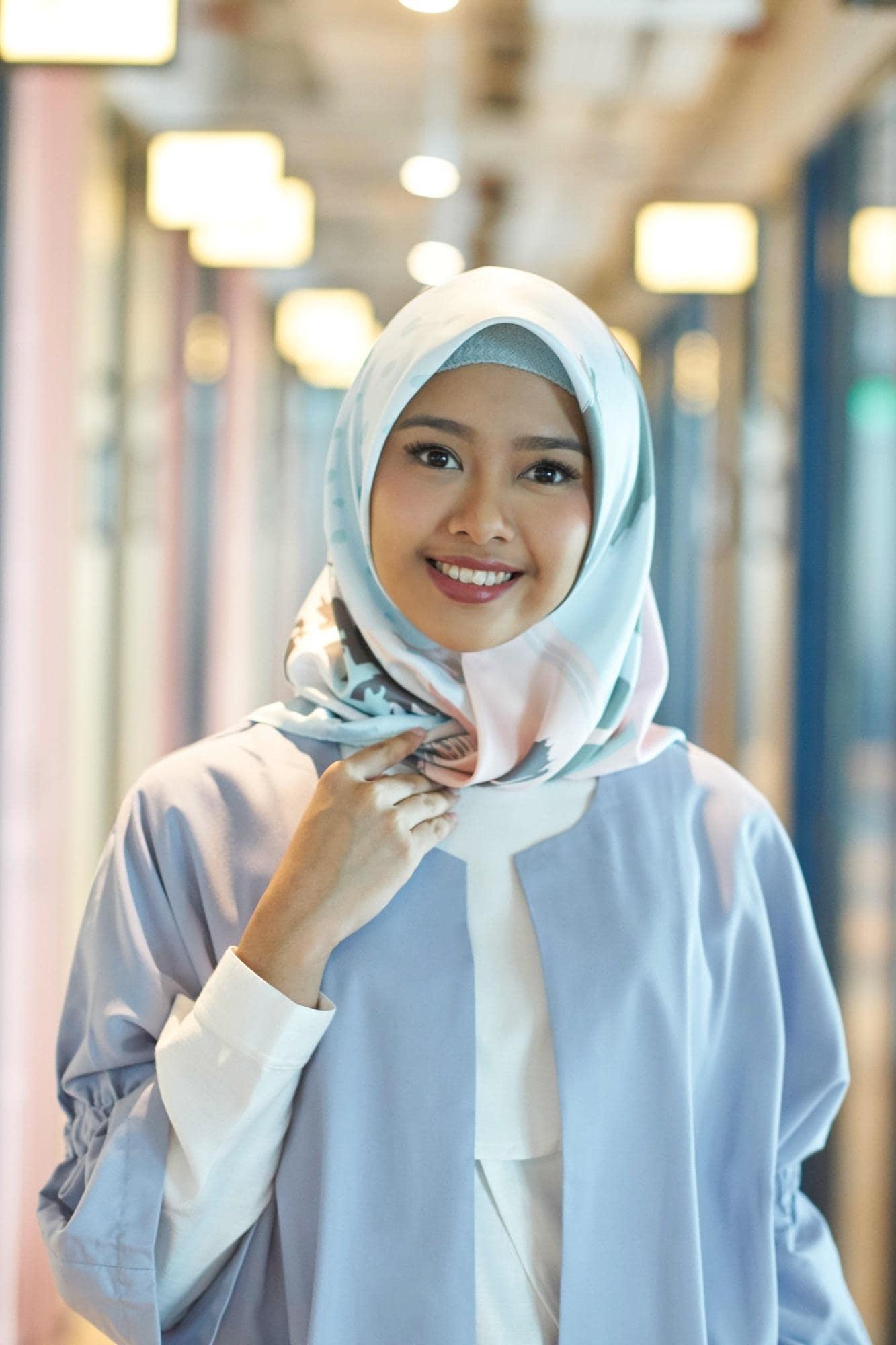 Wanita Asia memakai hijab segi empat motif