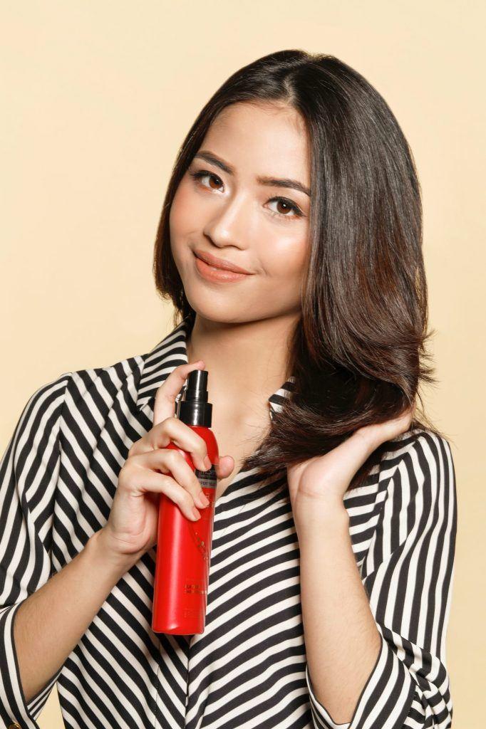 Wanita Asia menggunakan heat protection spray Tresemme