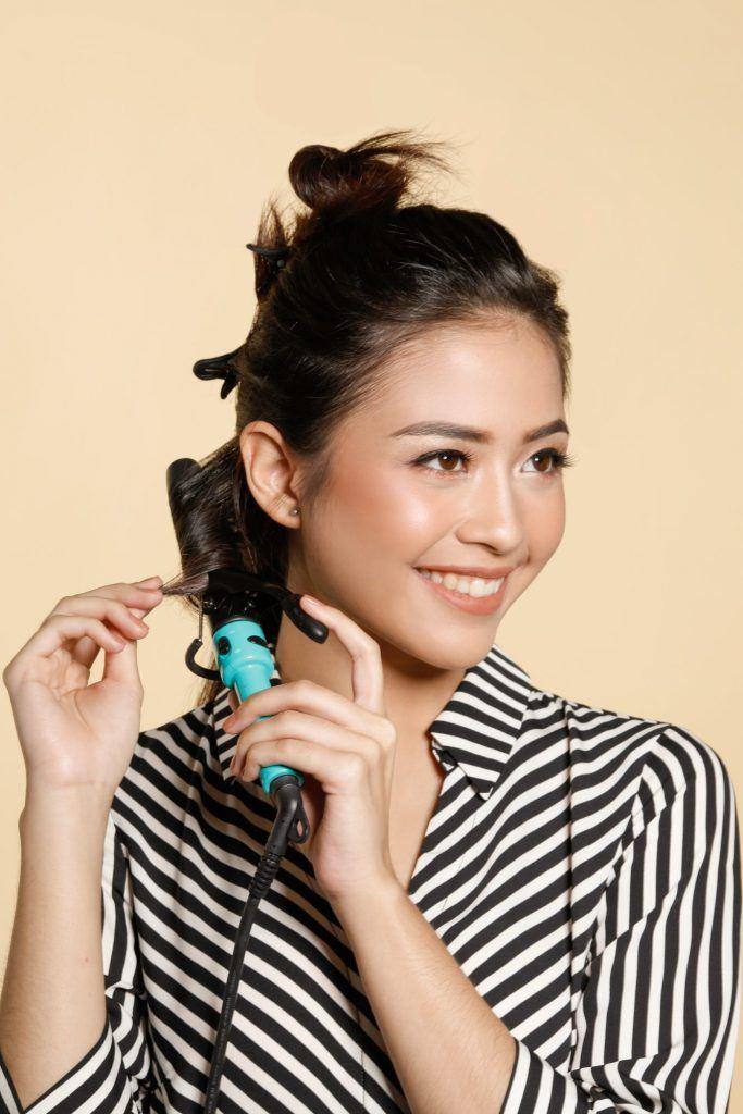 Wanita Asia mengeriting rambut dengan curling iron