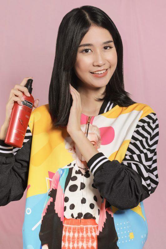 wanita asia berambut hitam pendek menyemprot heat protection spray