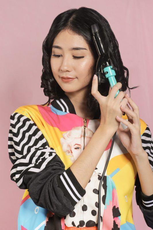 wanita asia berambut hitam sedang mencatok rambut