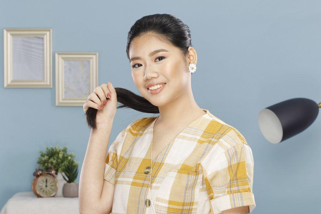 Wanita asia berambut hitam panjang diikat ponytail.