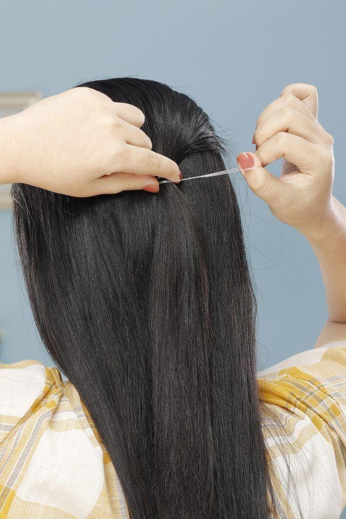 wanita asia berambut hitam panjang sedang mengikat rambut
