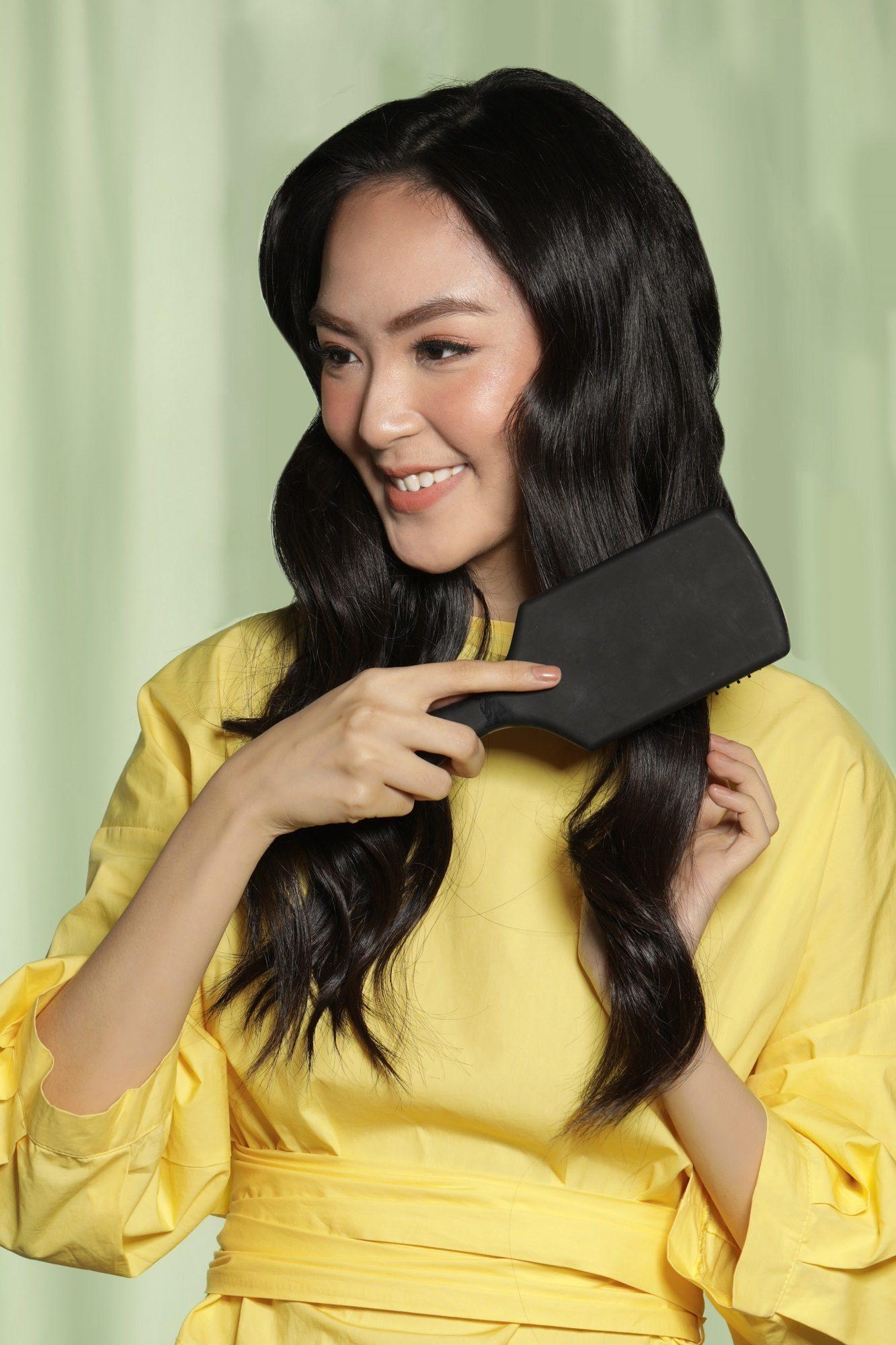 Wanita Asia menyisi rambutnya yang bergelombang.
