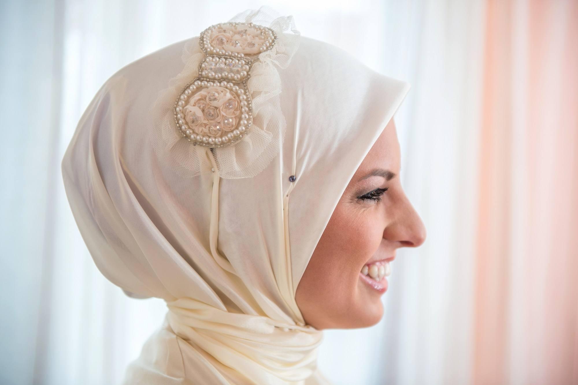 Wanita memakai hijab segi empat dan aksesori di kepalanya