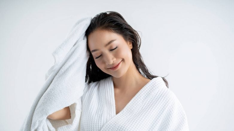 Wanita asia mengeringkan rambut dengan handuk