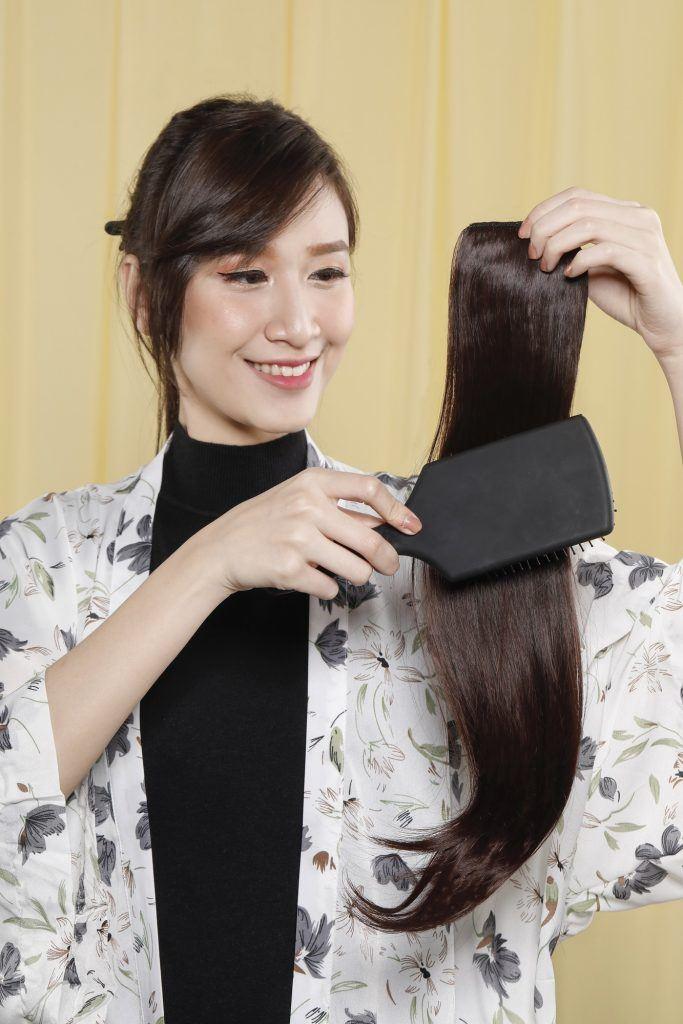 wanita asia menyisir rambut palsu sambungan