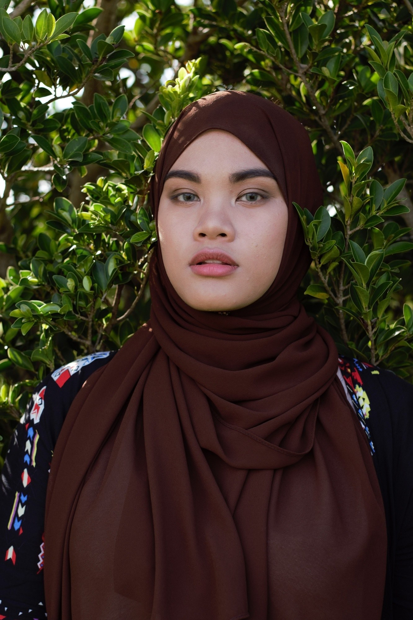 Wanita Asia memakai hijab sifon cokelat