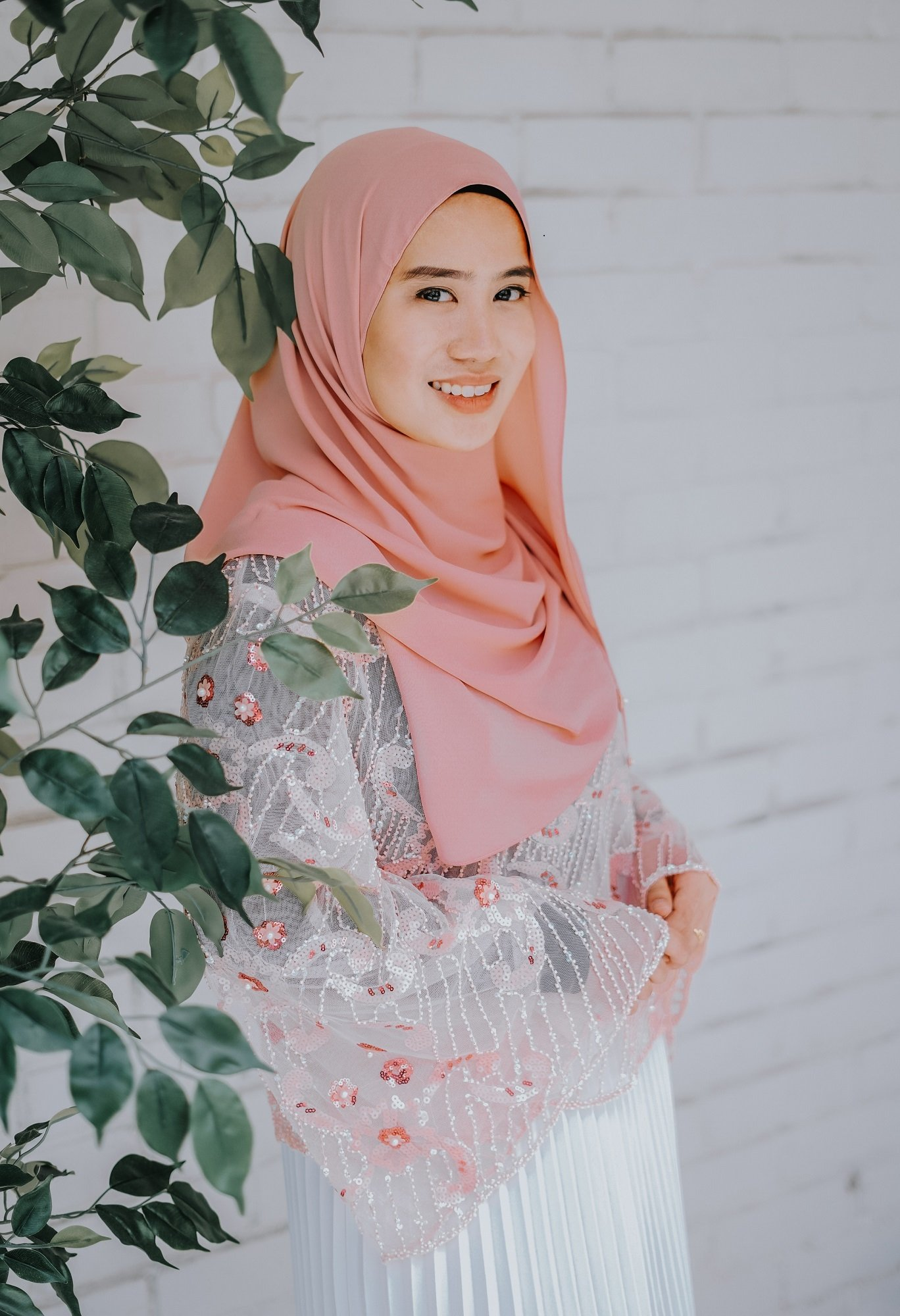 Wanita Asia memakai hijab pashmina pink dan tersenyum