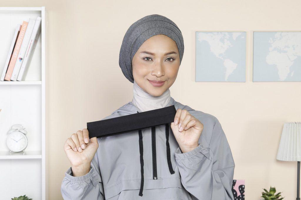 Wanita Asia memakai turban dan memegang bandana