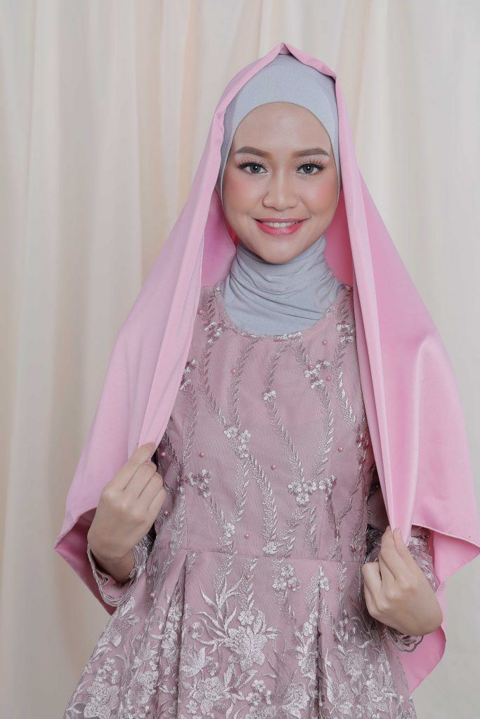Wanita Asia memakai ciput ninja membentangkan hijab satin