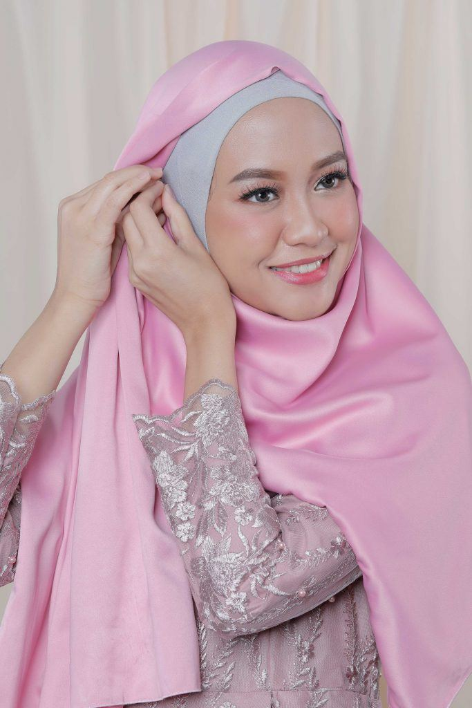 Wanita dengan hijab panjang menyempatkan jarum pentuk