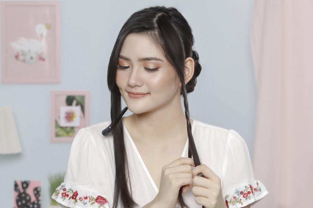 Wanita asia sedang membuat twist pada bagian samping wajah