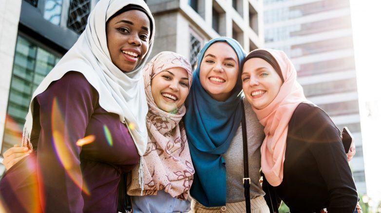 Empat wanita berbeda warna kulit memakai hijab dan tersenyum