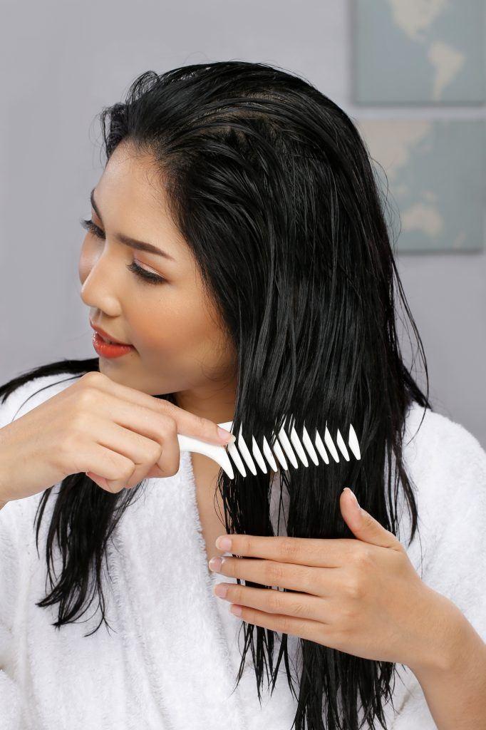 wanita asia dengan rambut panjang sedang menyisir rambut