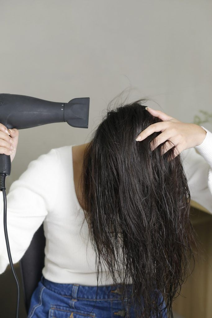 Wanita asia sedang mengeringkan rambut dengan hairdryer