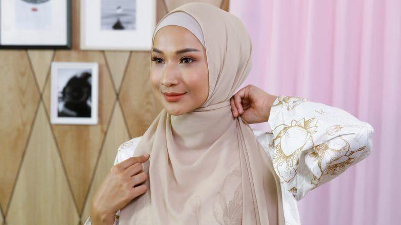 Wanita Asia merapikan hijab pashmina sifonnya.