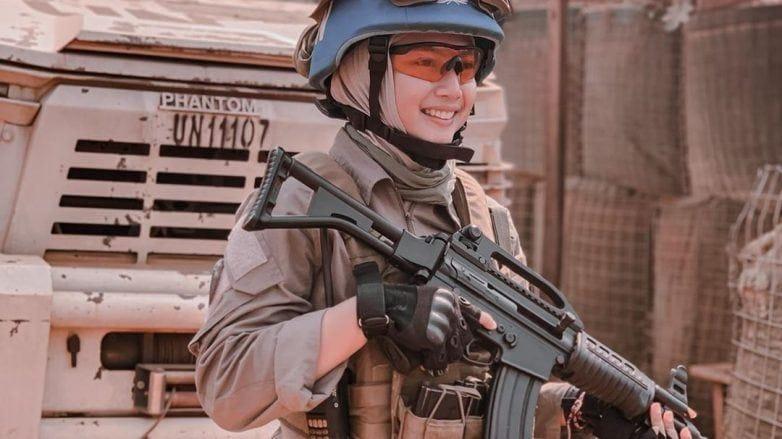 Briptu Hikma memegang senjata di depan mobil tentara