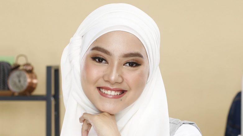 Wanita Asia memakai hijab putih dan tersenyum
