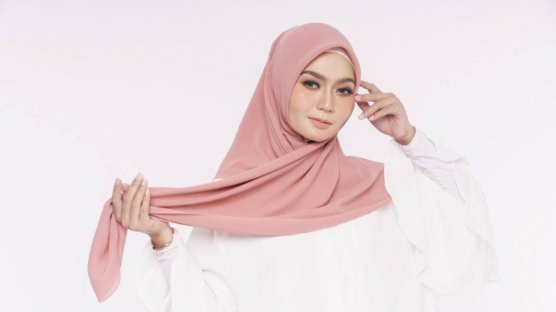 Wanita Asia memakai hijab segi empat warna peach.