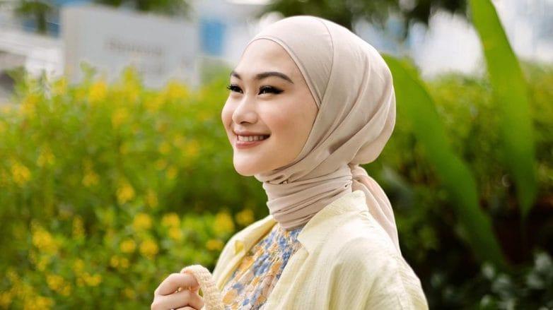 Indah Nada Puspita memakai baju dan tas serba kuning tersenyum di taman