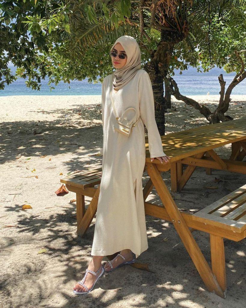 wanita hijaber memakai dress dan kacamata berdiri di pantai