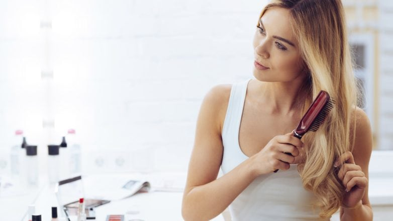 Mujer rubia cepillándose el pelo