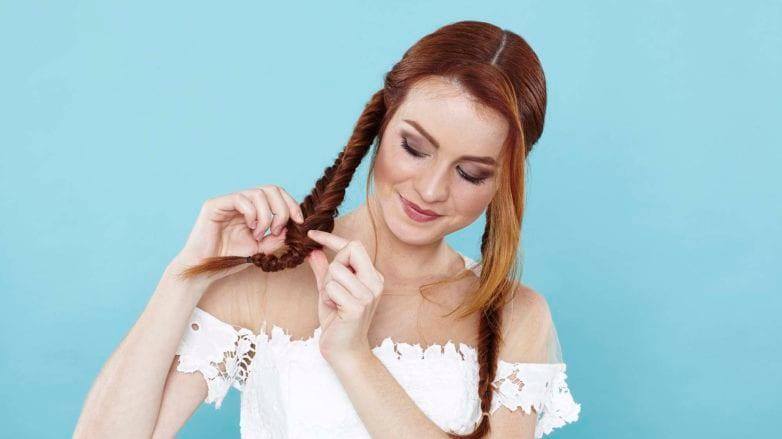 Chica de pelo rojo haciéndose una trenza