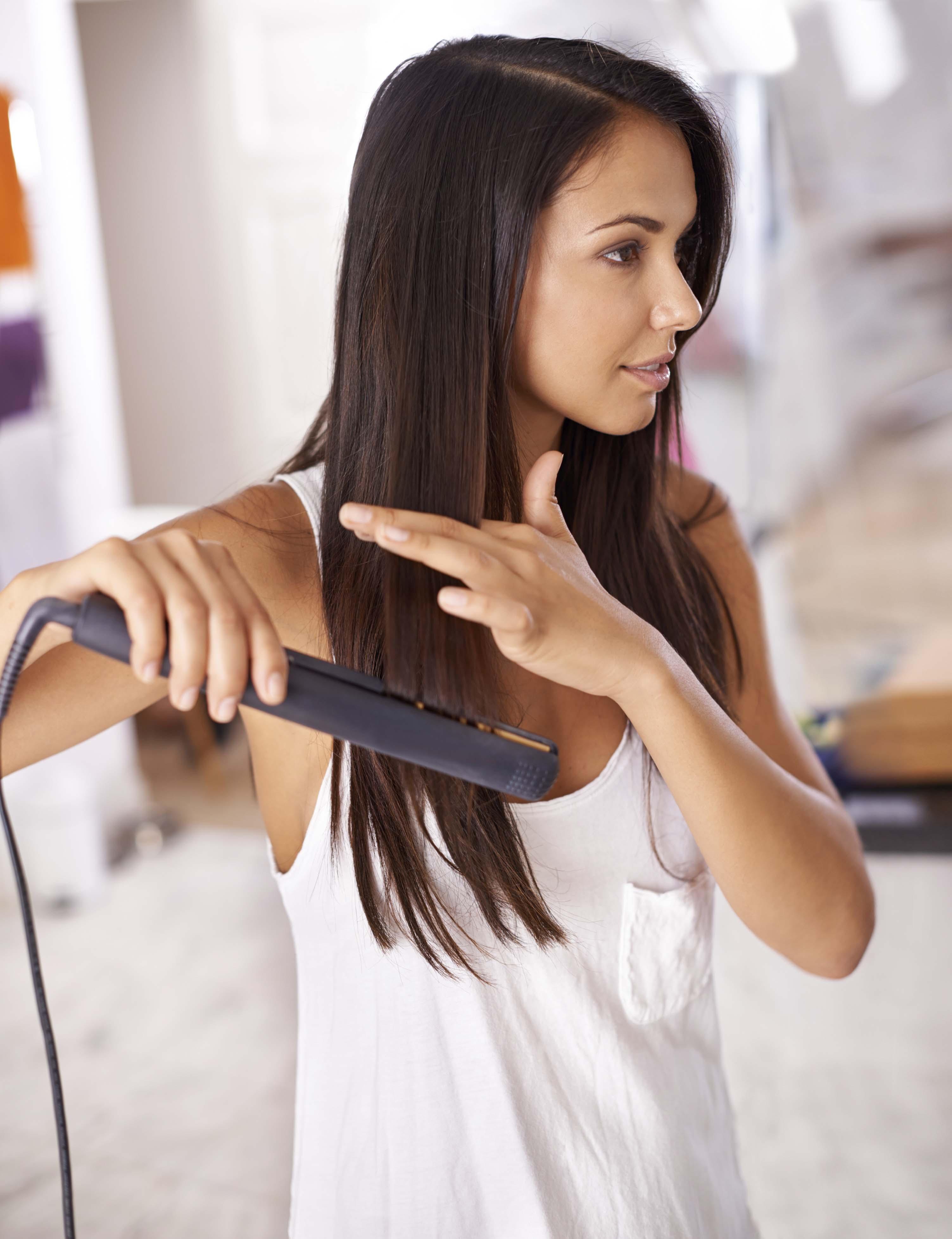 Chica planchándose el pelo