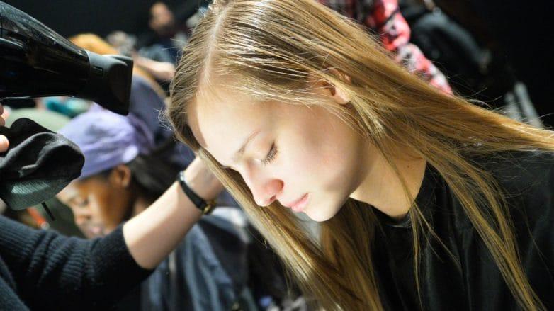 Peluquero secándole el pelo a una chica de cabello lacio castaño