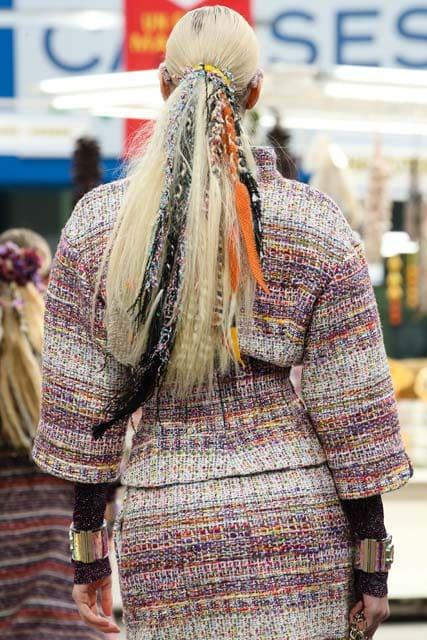 Peinado visto de espalda, coleta rubia con detalles de telas y otros agregados