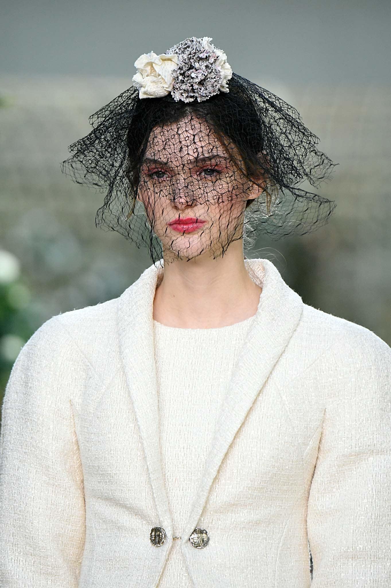 Cabello recogido castaño oscuro, cubierto por un adorno floral y un velo de encaje negro