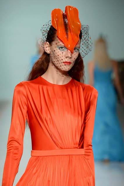 Mujer de cabello colorado con tocado negro y naranja que cubre parte de su rostro