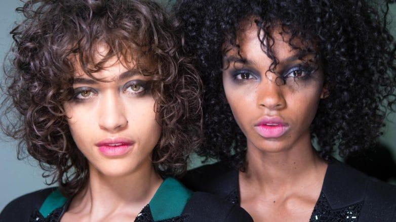 Dos mujeres de cabello muy enrulado, una castaña y una morocha